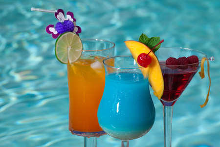 blue hawaiian drink: Mai Tai, Blue Hawaiian, and Cosmopolitan cocktails on swimming pool side Stock Photo