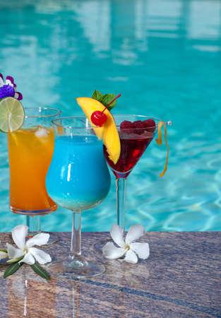 Mai Tai, Blue Hawaiian, and Cosmopolitan cocktails on swimming pool side Standard-Bild