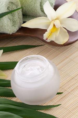 cremas faciales: Blanca flor de la orquídea Cymbidium y tarro de crema hidratante para el rostro de tratamiento de spa.