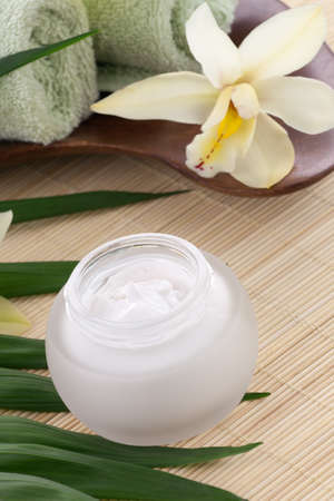 White Cymbidium orchid flower and jar of moisturizing face cream for spa treatment. photo