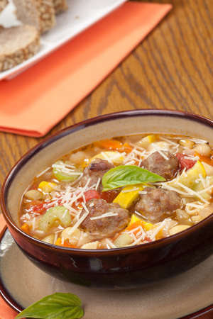 Closeup of bowl of hot fresh Italian Meatball Soup and wholegrain bread photo
