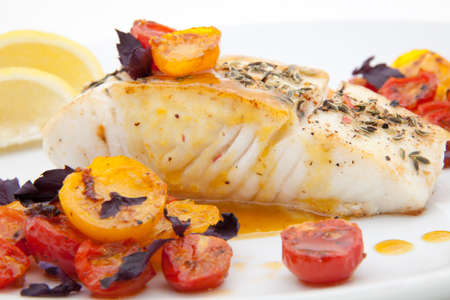 Pan fried halibut garnished with fennel seeds and spicy mustard sauce, served with fried cherry tomatoes salad with purple basil Reklamní fotografie