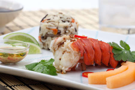 Closeup of delicious lobster tails served with spicy sauce, rice and melon