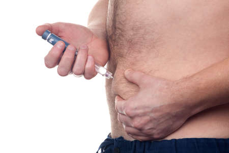 gets: Man with diabetes gets an insulin injection in abdomen area over white background.