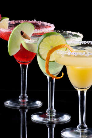 Three Margaritas - apple, orange and raspberry - in chilled glasses over black background, garnished with slice of green apple, limes, orange twist, raspberry and cinnamon stick  Most popular cocktails series  photo