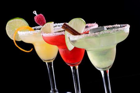 coctel margarita: Tres Margaritas - manzana, naranja y frambuesa-en vasos fríos sobre fondo negro, adornado con una rodaja de manzana verde, limón, twist de naranja, frambuesa y canela en rama serie de cócteles más populares