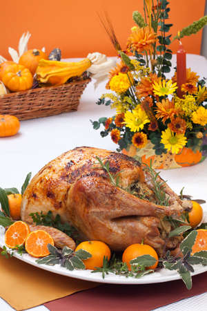 Garnished citrus glazed roasted turkey on holiday table, pumpkins, flowers, and white wine photo