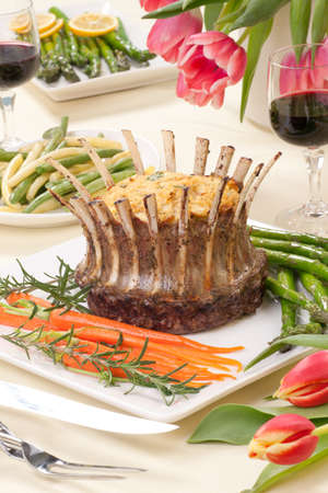 Crown roast of lamb with apple rosemary stuffing  Garnished with asparagus, glazed carrots, and rosemary twigs  Side dishes - asparagus, and beans  photo