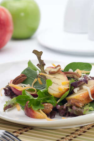 Closeup of salad with grilled apples, baby spinach, pecans, spring mix and chedar cheese served for healthy lunch photo