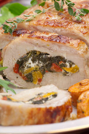 roulade: Feta-, spinach-, and bell pepper - stuffed pork tenderloin roulade garnished with sweet potato and green salad  Stock Photo