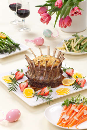 Crown roast of lamb with apple rosemary stuffing  Garnished with fresh strawberry, lemon, and rosemary twigs  Side dishes - asparagus, glazed carrots, and beans  photo
