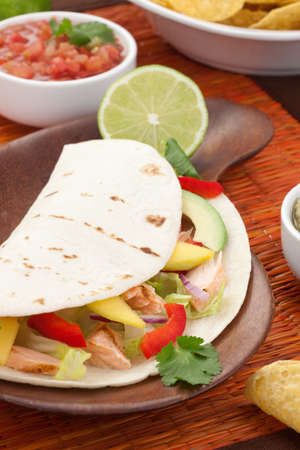 taco tortilla: Closeup of grilled salmon fish tacos served with guacamole, fresh tomatoes salsa, and tortilla chips
