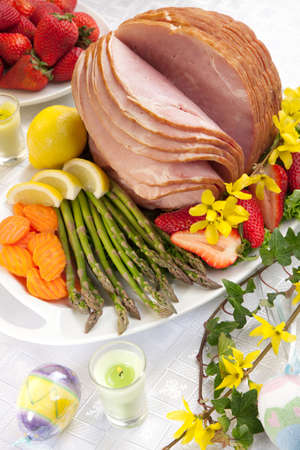 Table set with festive glazed ham for Easter celebration dinner garnished with asparagus, carrots, strawberry, and lemon wedges  版權商用圖片