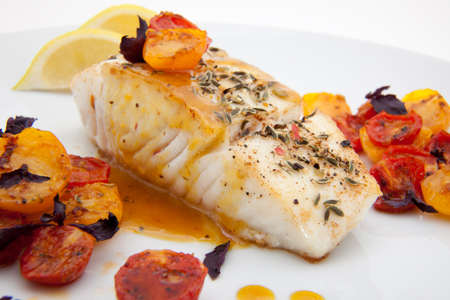Pan fried halibut garnished with fennel seeds and spicy mustard sauce, served with fried cherry tomatoes salad with purple basil Stok Fotoğraf