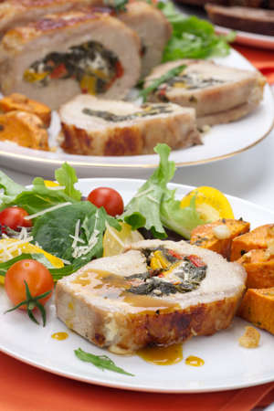 Feta-, spinach-, and bell pepper - stuffed pork tenderloin roulade garnished with sweet potato and green salad Stock Photo - 12958392