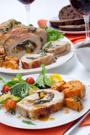 Feta-, spinach-, and bell pepper - stuffed pork tenderloin roulade garnished with sweet potato and green salad  photo