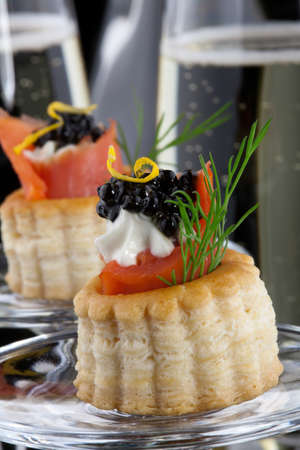 Closeup of black caviar on Creme Fraiche and smoked salmon canape and flutes of Champagne over black background  photo