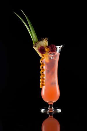 Fancy Rum Runner cocktail over black background on reflection surface, garnished with pineapple flag, fresh raspberry, and orange twist  Most popular cocktails series Stock Photo - 12958396
