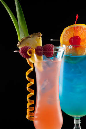 shaken: Rum Runner and Blue Lagoon cocktaisl over black background on reflection surface, garnished with pineapple flag, fresh raspberry, maraschino cherry, and orange twist  Most popular cocktails series
