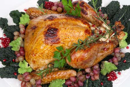 Glazed roasted turkey garnished with grapes, pomegranates, and broccoli over white background photo