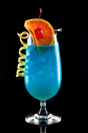 Bright Blue Lagoon cocktail over black background on reflection surface, garnished with orange slice.