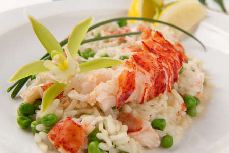 Lobster and green pea Risotto garnished with chives, lemon, and orchid flower