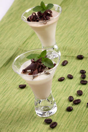 Closeup of Coffee Vanilla Panna Cotta Dessert in glass garnished with dark chocolate shavings, and fresh mint  photo