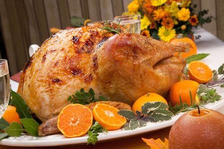naranjas: Cítricos adornado vidriosos pavo asado en la mesa durante las fiestas, las calabazas, flores y vino blanco