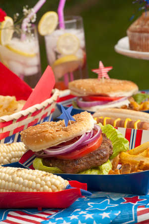 july: Hot dogs, corn and burgers on 4th of July picnic in patriotic theme Stock Photo