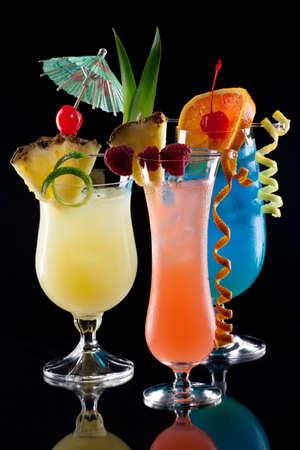 coctel de frutas: Rum Runner, Bahama Mama, y ??cocktaisl Laguna Azul sobre fondo negro en la superficie de reflexión, adornado con la bandera de la piña, frambuesa fresca, cerezas al marrasquino, y toque de limón serie de cócteles más populares