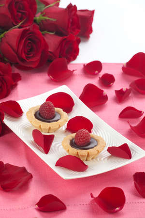 Closeup of delicious fresh raspberry chocolate petite cakes on Valentine day  Red roses and petals around Stock Photo - 13566458