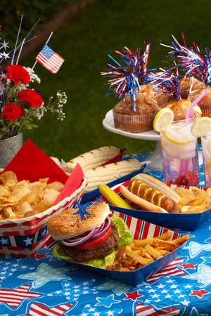 juli: Hotdogs, maïs en hamburgers op 4 juli picknick in patriottische thema Stockfoto