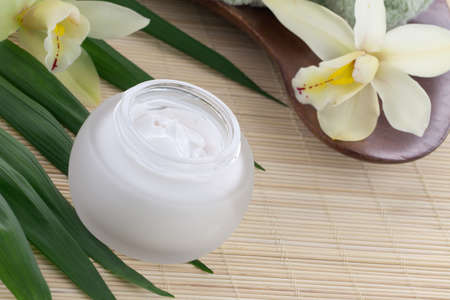 White Cymbidium orchid flower and jar of moisturizing face cream for spa treatment  Stock Photo