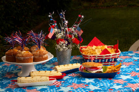 Cornbread, corn and burgers on 4th of July picnic in patriotic theme photo