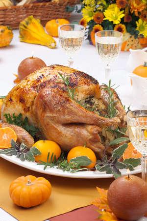 Garnished citrus glazed roasted turkey on holiday table, pumpkins, flowers, and white wine Stock Photo - 13719731