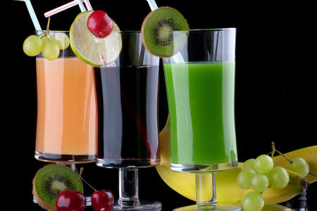 Glasses of organic juice made from fresh fruits and surrounded by fresh ones  Series about organic and healthy drinks