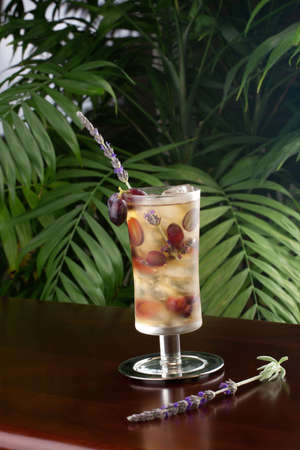 non: Closeup of glass of lavender and grapes iced tea garnished with lavender twig on a table in a restaurant on a tropical beach  Stock Photo