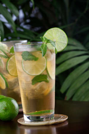 non: Two glasses of lime and mint iced tea garnished with lime and mint on a table in a restaurant on a tropical beach
