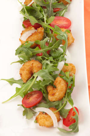 Popcorn shrimp and baby arugula salad with grape tomatoes and white sweet onions  photo