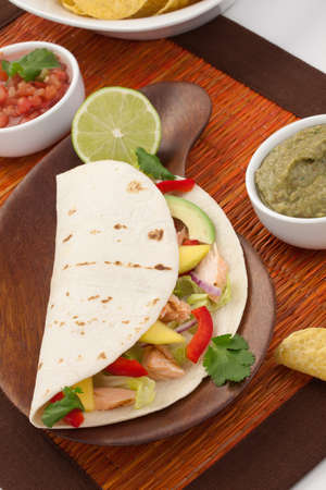 corn tortilla: Closeup of grilled salmon fish tacos served with guacamole, fresh tomatoes salsa, and tortilla chips