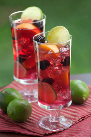 alcoholic drink: Closeup of two glass of Red Sangria - apricot, lime and blackberry - on outside table  Stock Photo