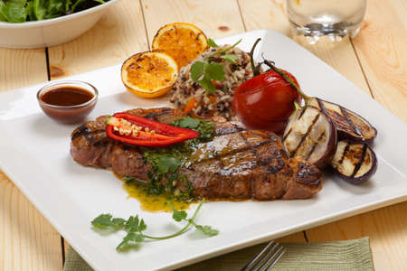 Close of of one piece cut of medium rare grilled steak with spicy herb sauce, garnished with grilled vegetables and organic brown rice