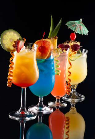 Tequila Sunrise, Blue Lagoon, Rum Runner, en Bahama Mama cocktails over zwarte achtergrond op reflectie oppervlak, gegarneerd met aardbei, limoen, ananas vlag, verse frambozen, maraschino cherry en lime twist meeste populaire cocktails serie