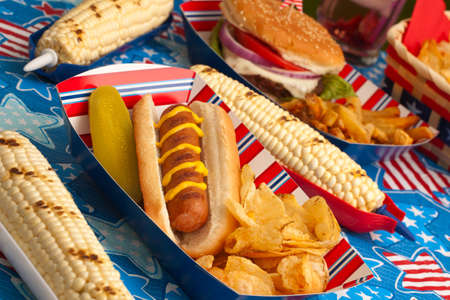corn salad: Hot dogs, corn and burgers on 4th of July picnic in patriotic theme Stock Photo