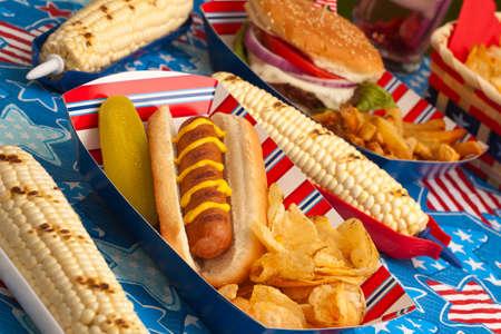 Würstchen, Mais und Burger am 4. Juli Picknick im patriotischen Thema Standard-Bild