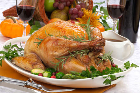 roasted turkey: Garnished roasted turkey on fall festival decorated table with horn of plenty and red wine Stock Photo