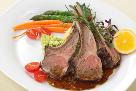 lamb chop: Rosemary roasted lamb chops (ribs) garnished with asparagus, glazed carrots,, grape tomatoes, and micro greeens.  Stock Photo