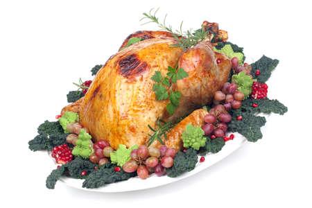 Glazed roasted turkey garnished with grapes, pomegranates, and broccoli over white background