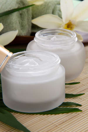 White Cymbidium orchid flower and jar of moisturizing face cream for spa treatment  photo