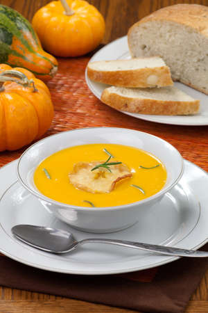 Closeup of bowls of hot delicious pumpkin soup with roasted apples, and rosemary